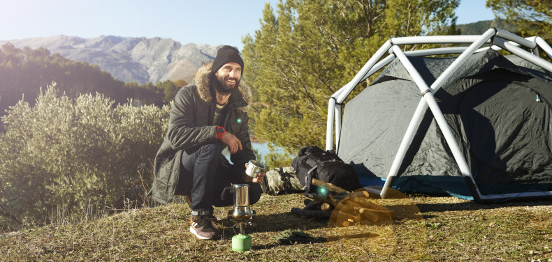 Adventure hiking man with coffee and backpack relaxing after outdoor activity.  Hikers sitting in grass near tent smiling happy outdoors in mountain forest enjoying sun. Lifestyle photo of Caucasian breaded man. Conceptual scene.